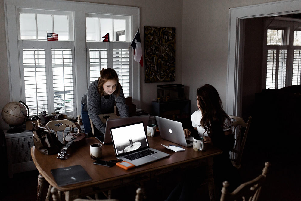 Stock image of two women working on laptops from a table at home