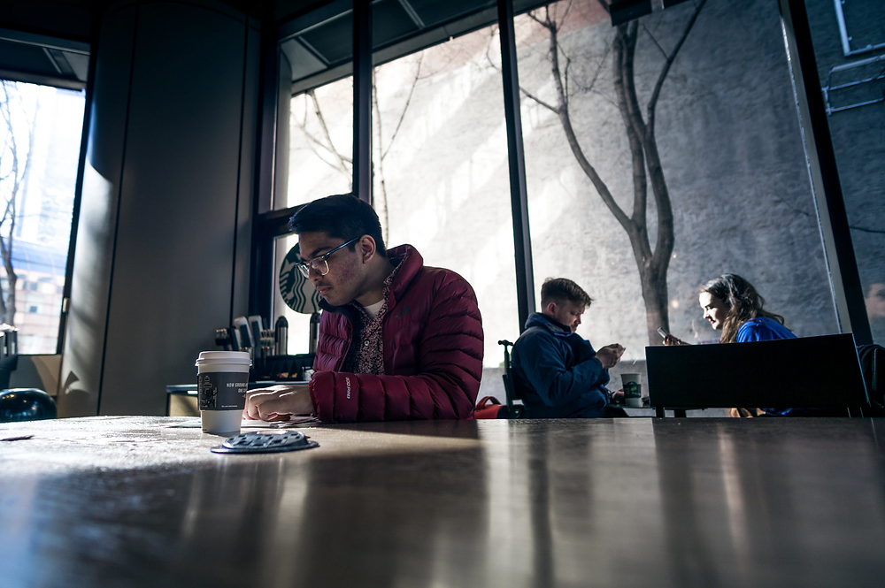 Stock photo of man in jacket sitting in coffee shop working on a tablet and notebook