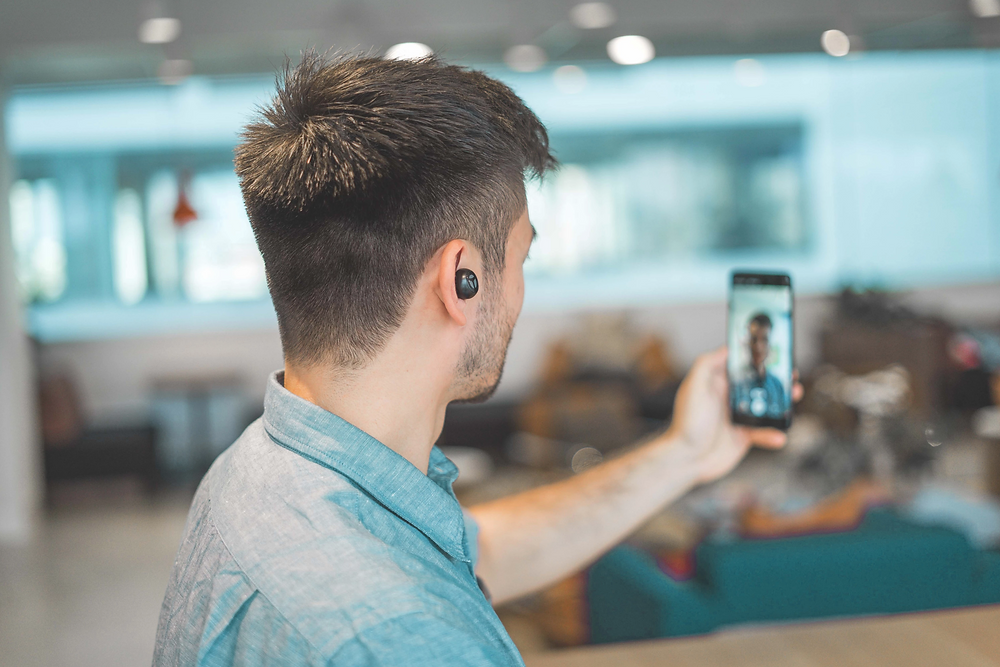 Stock image of man with earbuds having a video call with coworker on his phone