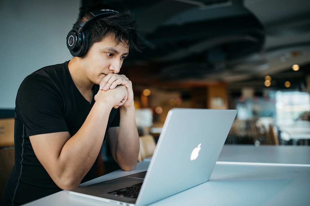 Stock image of man with headphones working on a laptop in office
