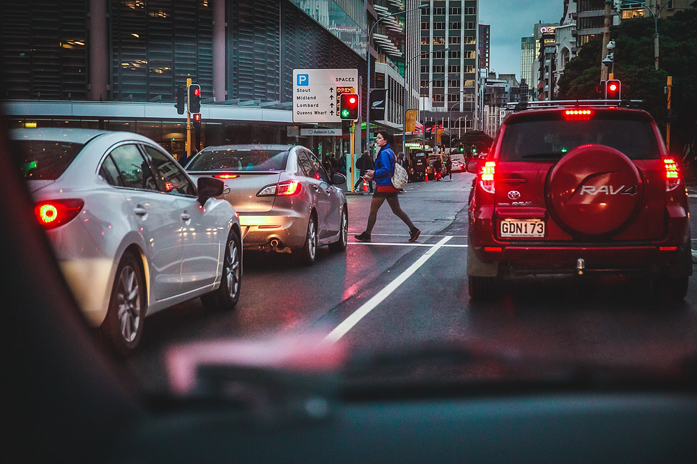 Stock image of traffic with cars stopped at red light and person walking across the crosswalk