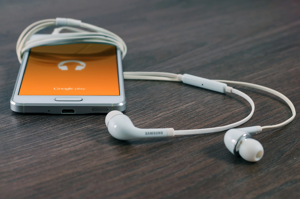 Stock image of mobile phone with headphones and Google Play