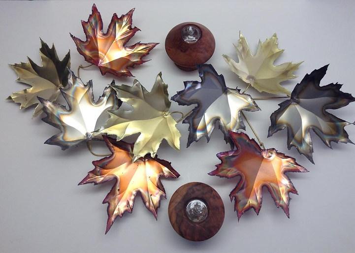 Copper, Brass, and Nickel Large Maple Leaves shown flat with 2 Redwood Tea Lights