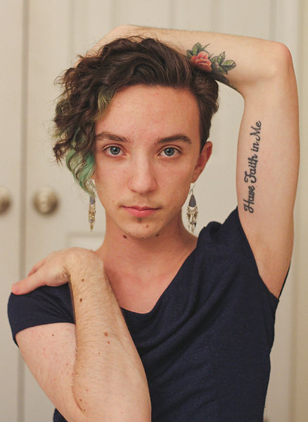 Chandler has brown and green curly hair. They wear a purple dress with purple dangly earrings. They are looking directly into the camera. One hand is on their shoulder, the other behind their head, exposing their flower tattoo.