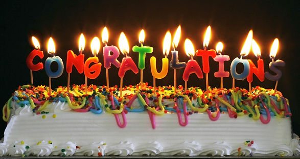 cake with lit candles spelling congratul