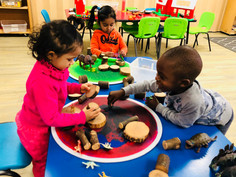 Children using wooden logs to create homes for dinosaurs