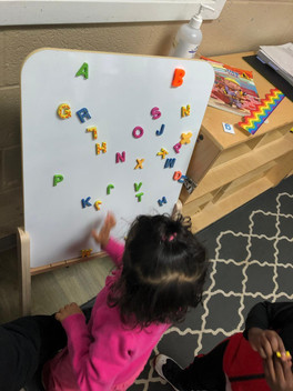 Child M using alphabet magnets to practice her letters