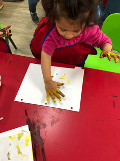 Child M is getting ready to stamp her yellow-painted hand on the paper