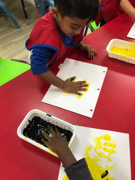 Choosing between two colors, the children are enjoying hand-painting