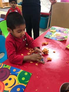 Child S applying playdough on the people structure toy