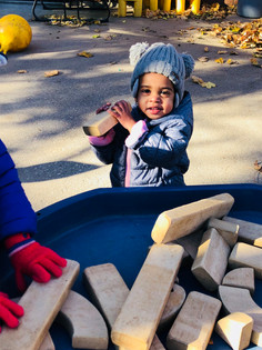 Child M using wooden bricks to build her structure