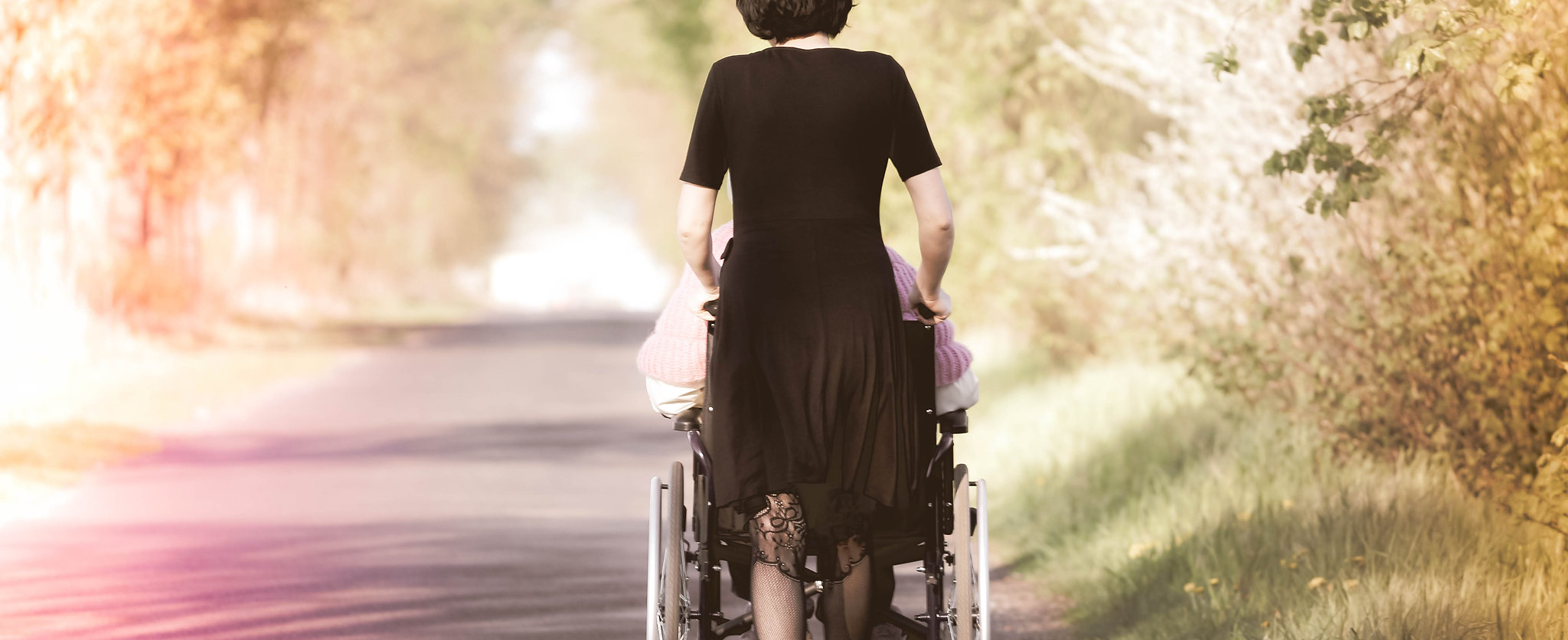 A woman pushing a wheelchair with a disa