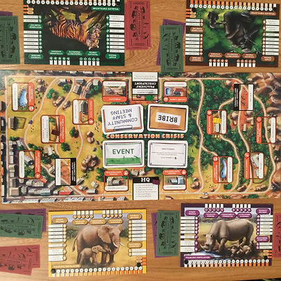 The wildlife-themed family board game Conservation Crisis on a wooden table ready to play