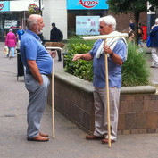 Two Men in Blue Discussing Brushes