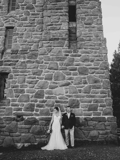 Black and white portrait of the bride and groom at the base of Mt. Constitution tower.