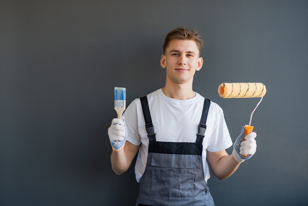 Handsome young interior painter holding a paint roller