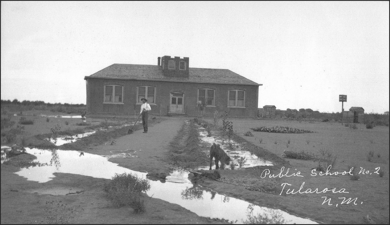 Tularosa Public School #2.  Once this school resided on Clayton Lane.  Spotted is a canine playing in the irrigation waters and also a possible basketball hoop.