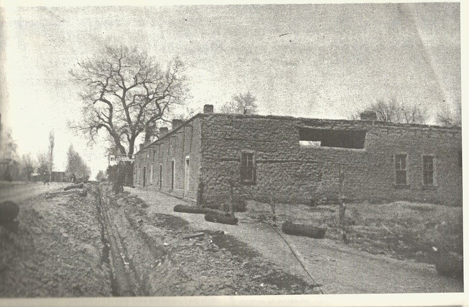 El fuerte (The Fort) as this structure that grew out of the original Tularosa chozas became known, in 1903, only 41 years after Tularosa was founded. It is believed that this photo was taken when the wood water mains were replaced in 1903. The Sandoval store is directly across the street. This location is on east side of 4th street (now US Highway 70) between Fresno and Granado streets.