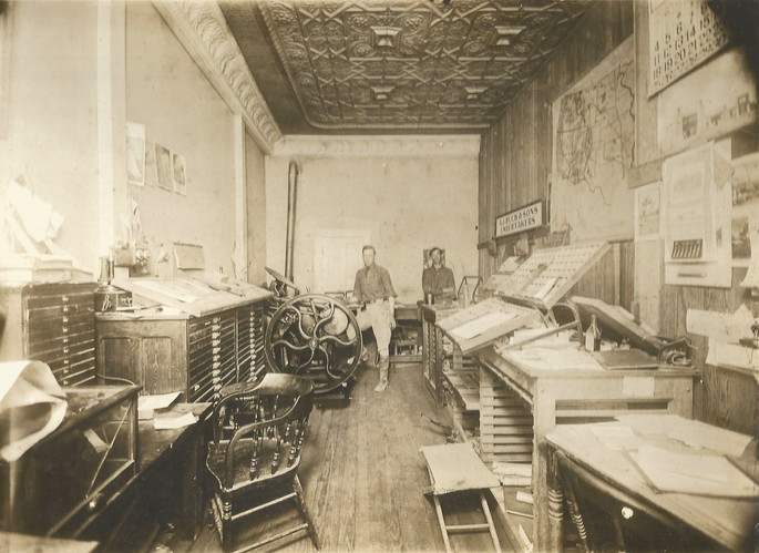 "A Tularosa printing & publishing company in April, 1915. Notice the Chicago Genuine, non-dial, straight shaft, desk stand oil-can ""Candlestick"" style telephone sitting on the printing press cabinet on the left. It appears the business is in a subdivided building by the looks of the ceiling."