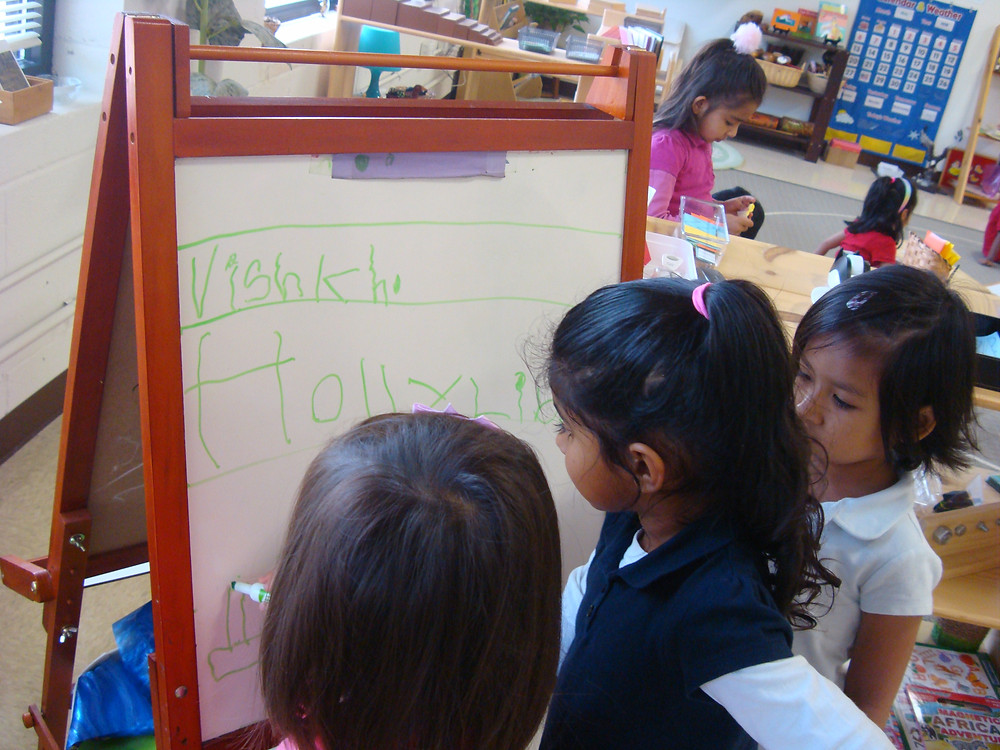 socialization-skills-in-children-girls-writing-on-whiteboard-together