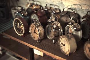 Despertadores antigos de metal sobre uma mesa.