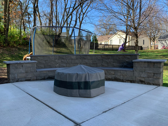 Custom backed seating wall with custom pillars and firepit