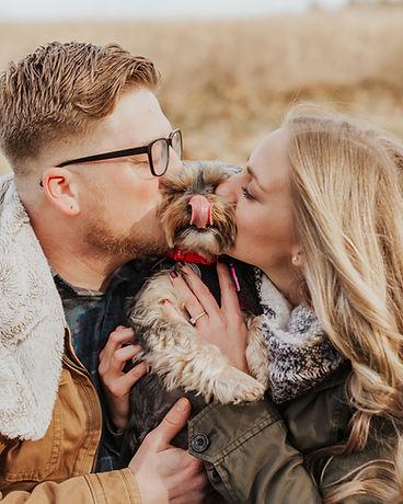 engaged couple kissing dog
