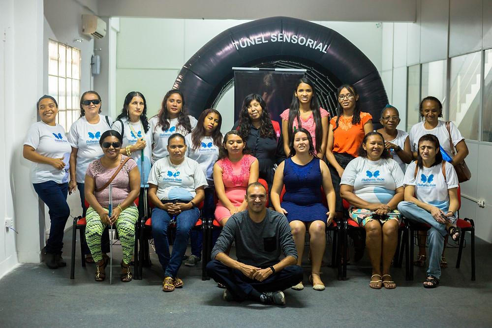 Fotografia posada com as beneficiadas do projeto com o professor Iraildon Mota, e ao fundo o Túnel Sensorial.