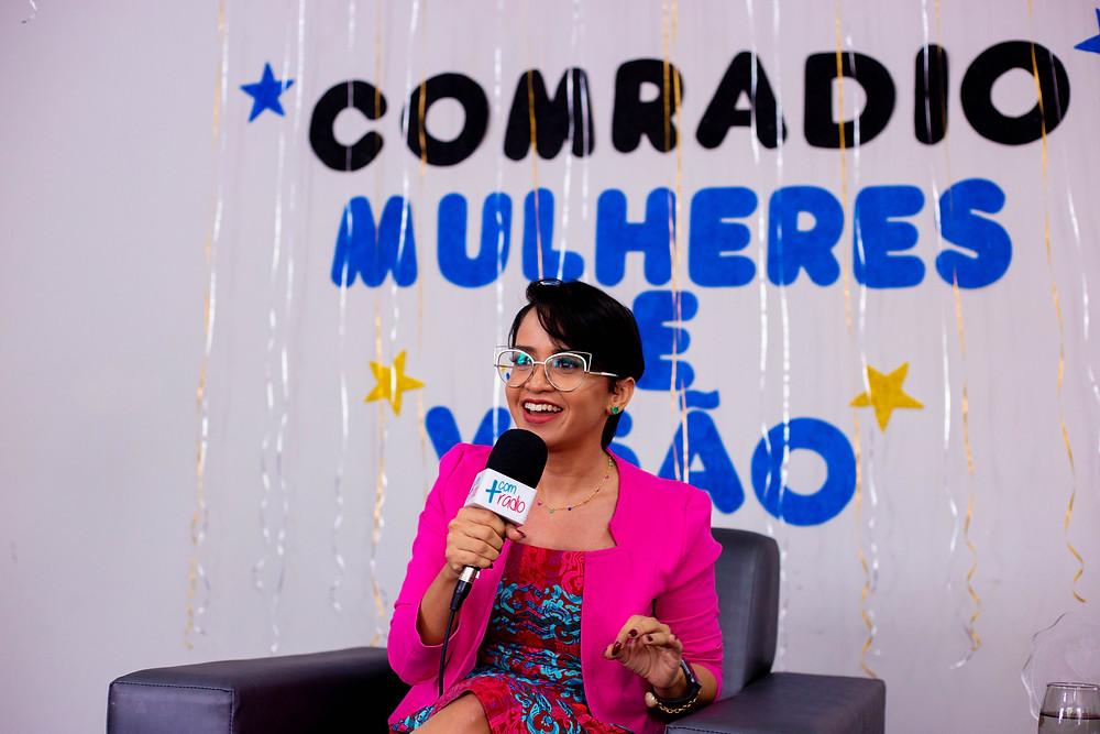 A Jornalista Sávia Barreto sentada falando ao microfone. E atrás na parede: Comradio - Mulheres de Visão