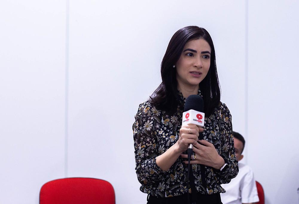 A médica Graziela Viana falando ao microfone para os presentes na confraternização.