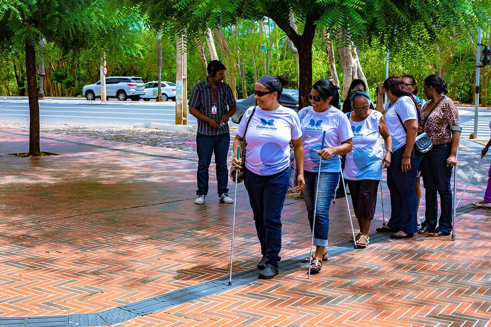 Fotografia aparecendo as beneficiadas do projeto, algumas com a camisa farda, andando no piso tátil.