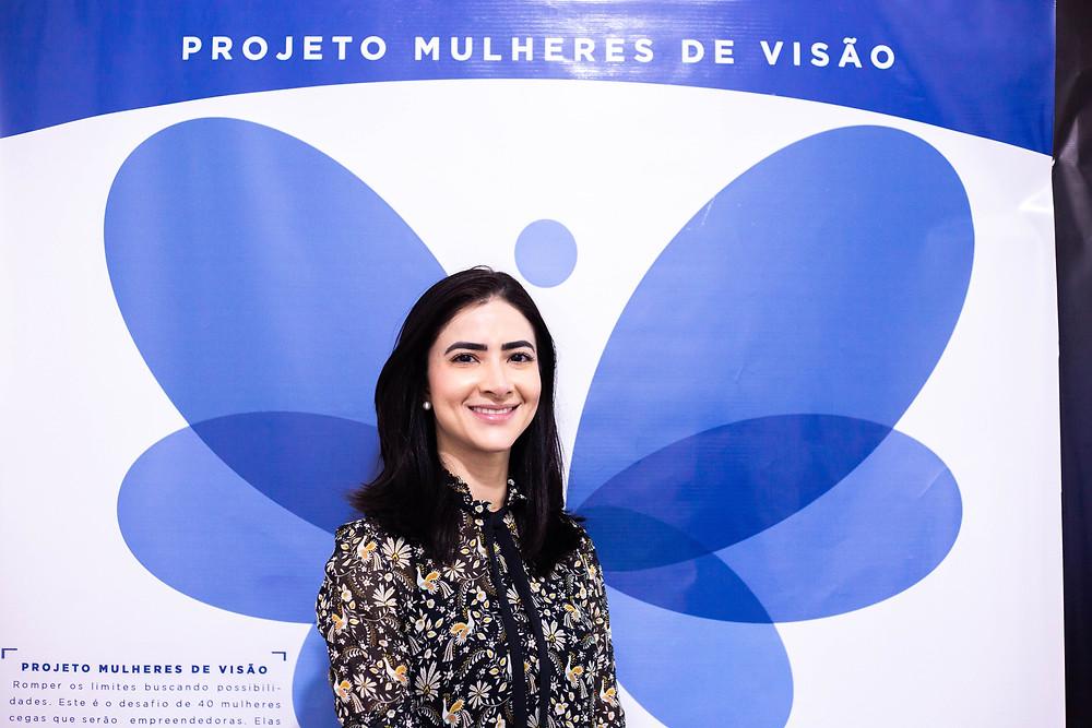 A médica oftalmologista, Graziela Viana, pousando para foto em frente a um banner que tem uma borboleta, símbolo do projeto.