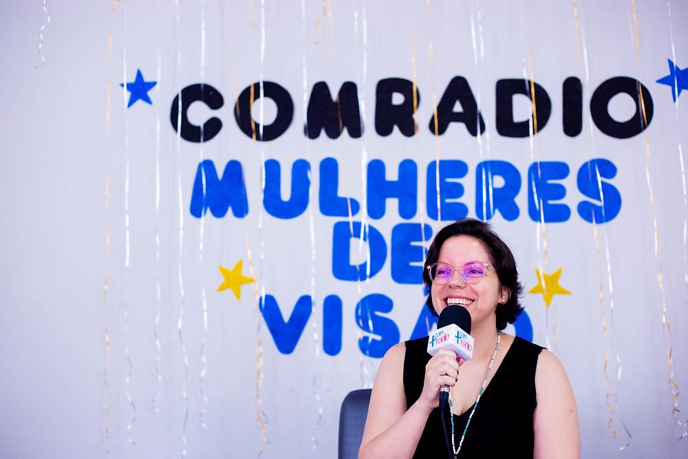 Doutora Carla Yásca sentada falando ao microfone. E na parede: Comradio - Mulheres de Visão