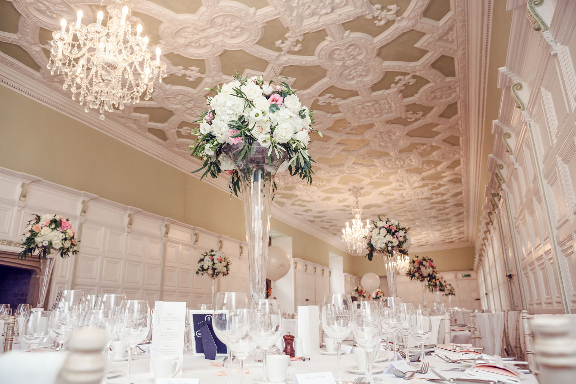 Compact, luxuriant and elegant tall table arrangements in the Long Gallery.