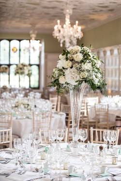 Showcasing a stunning tall table design in a regal trumpet vase.  A fanfare for the married couple.