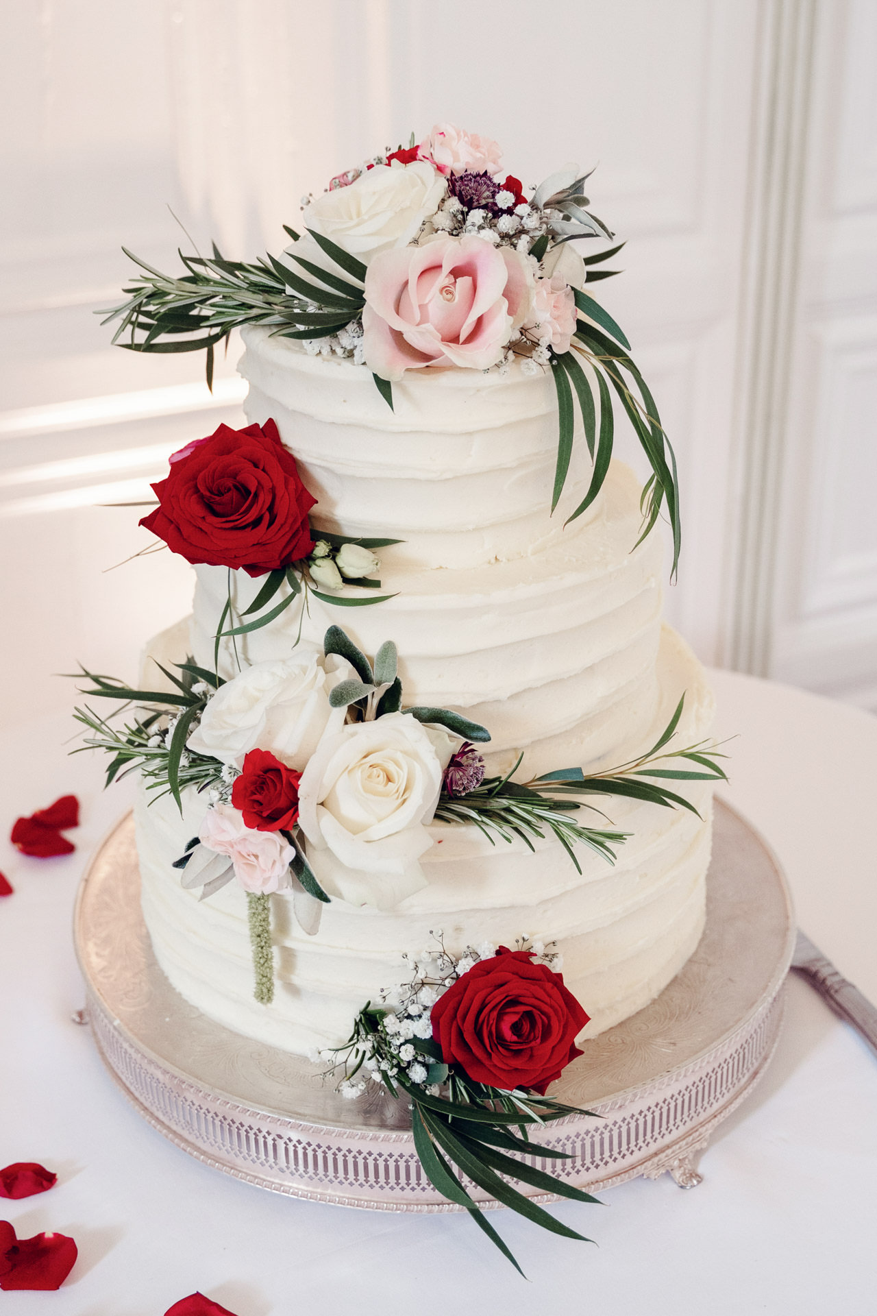 Simple but effective flowers and foliage can add opulence to a plainer wedding cake.