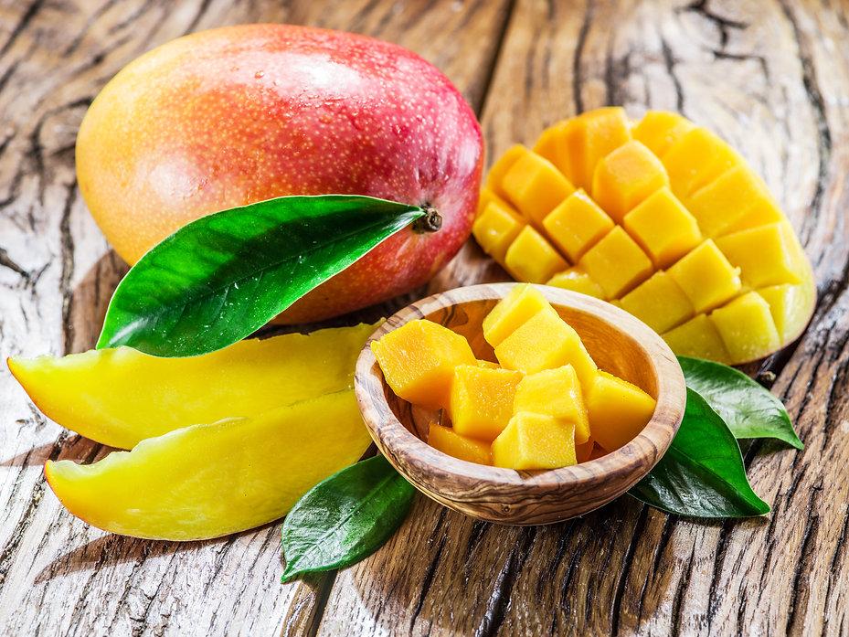 Mango fruit and mango cubes on the woode