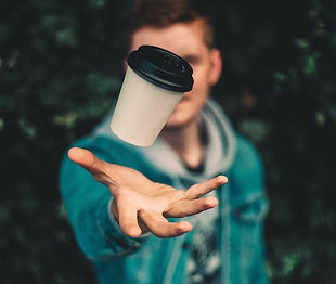 Man throwing disposable coffee cup