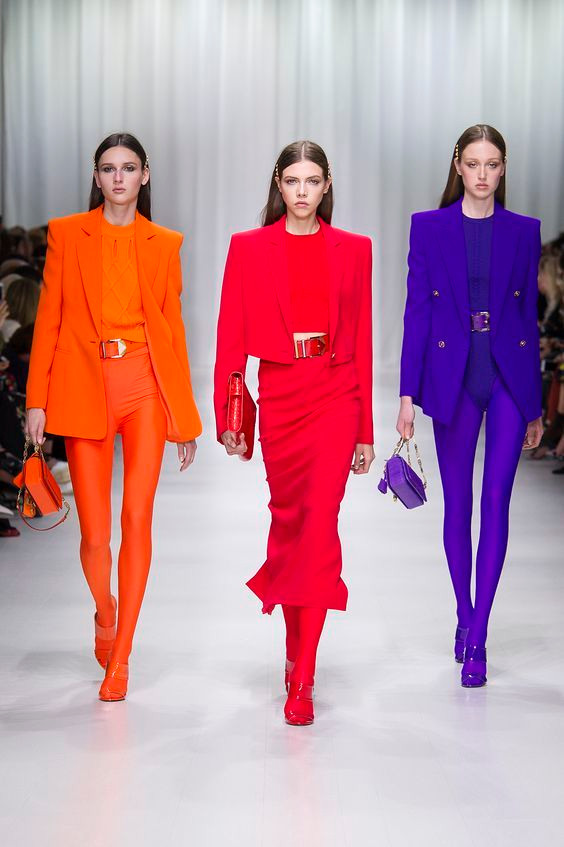 Models in bright colorful outfits on the runway