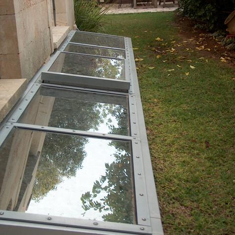 חצר אנגלית- סקיילייט חד שיפועי עם חלון חשמלי נפתח