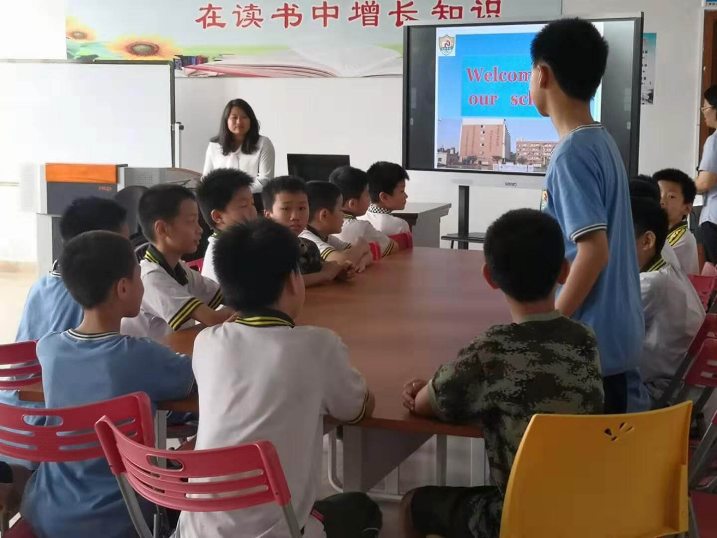 Ming listens to a question while presenting to children at a school
