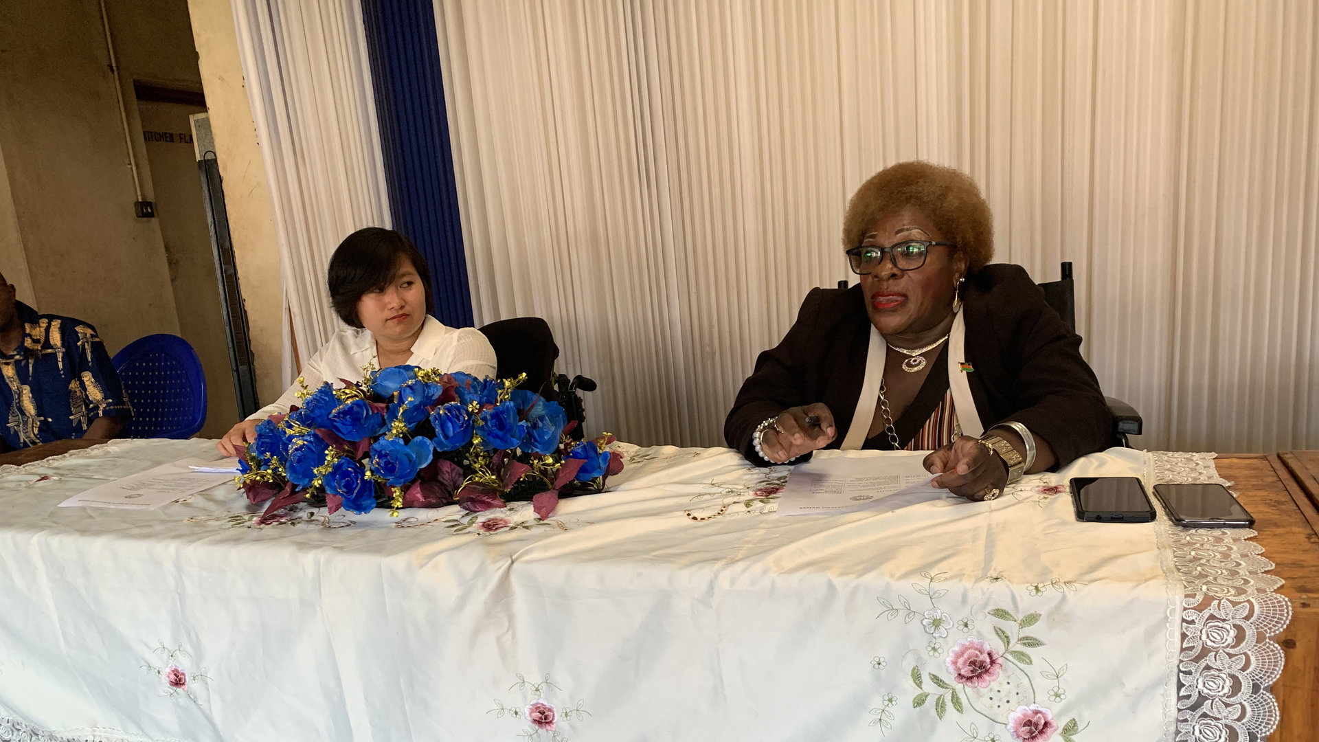 Ming and another woman speak from a table