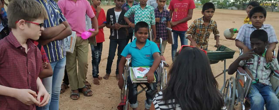 Ming meets a small group of children, some of them in wheelchairs