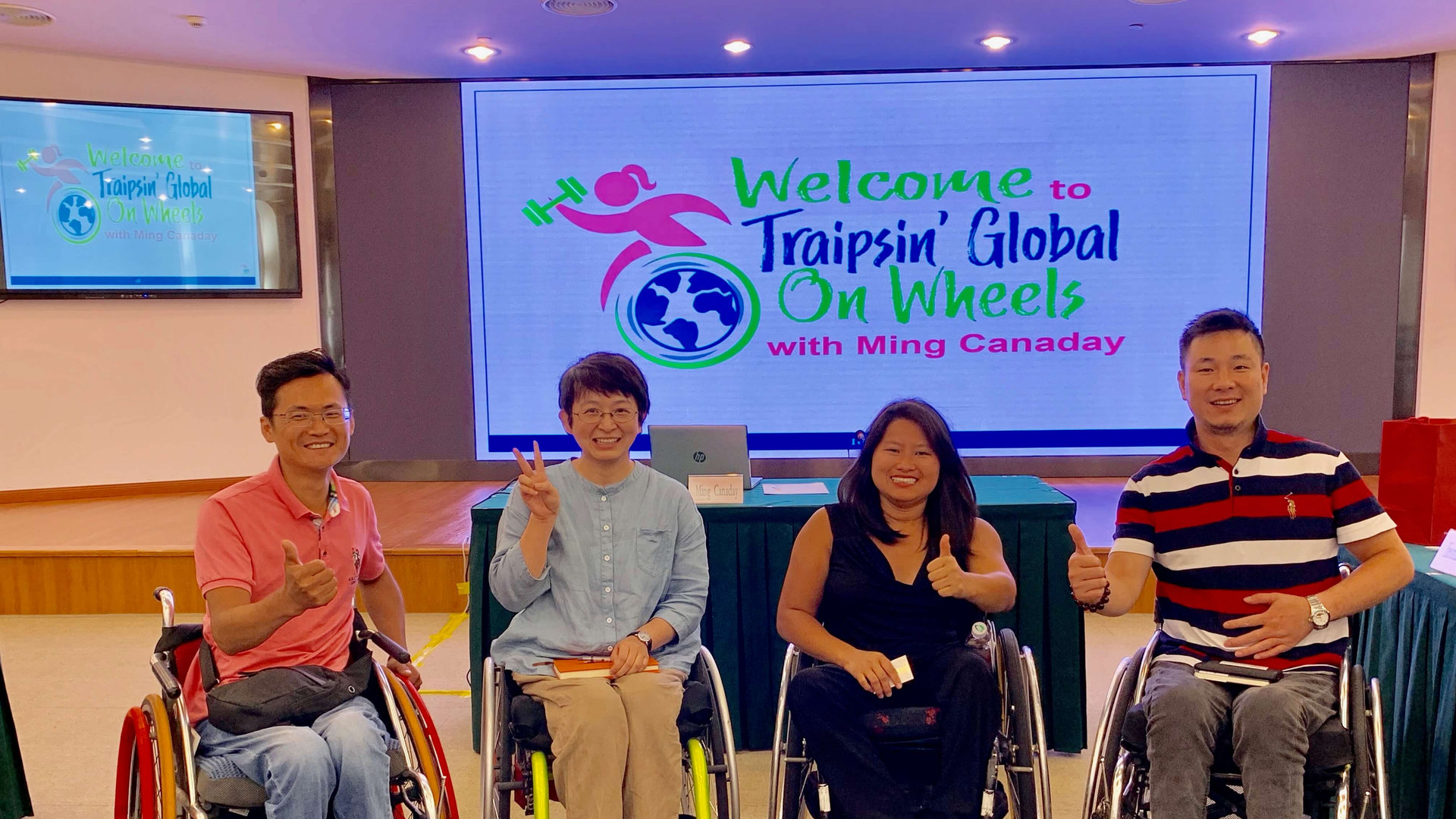 Ming and others in wheelchairs giving thumbs up signs