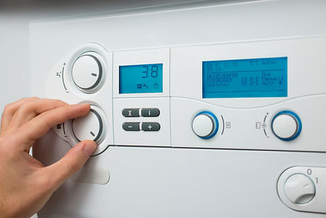 Person turning on a gas boiler