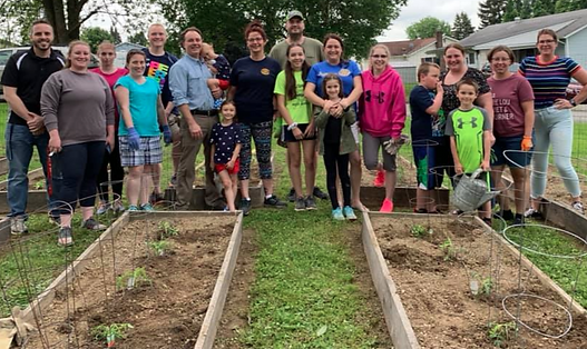 ROW members and their kids take a break from prepping vegetable beds
