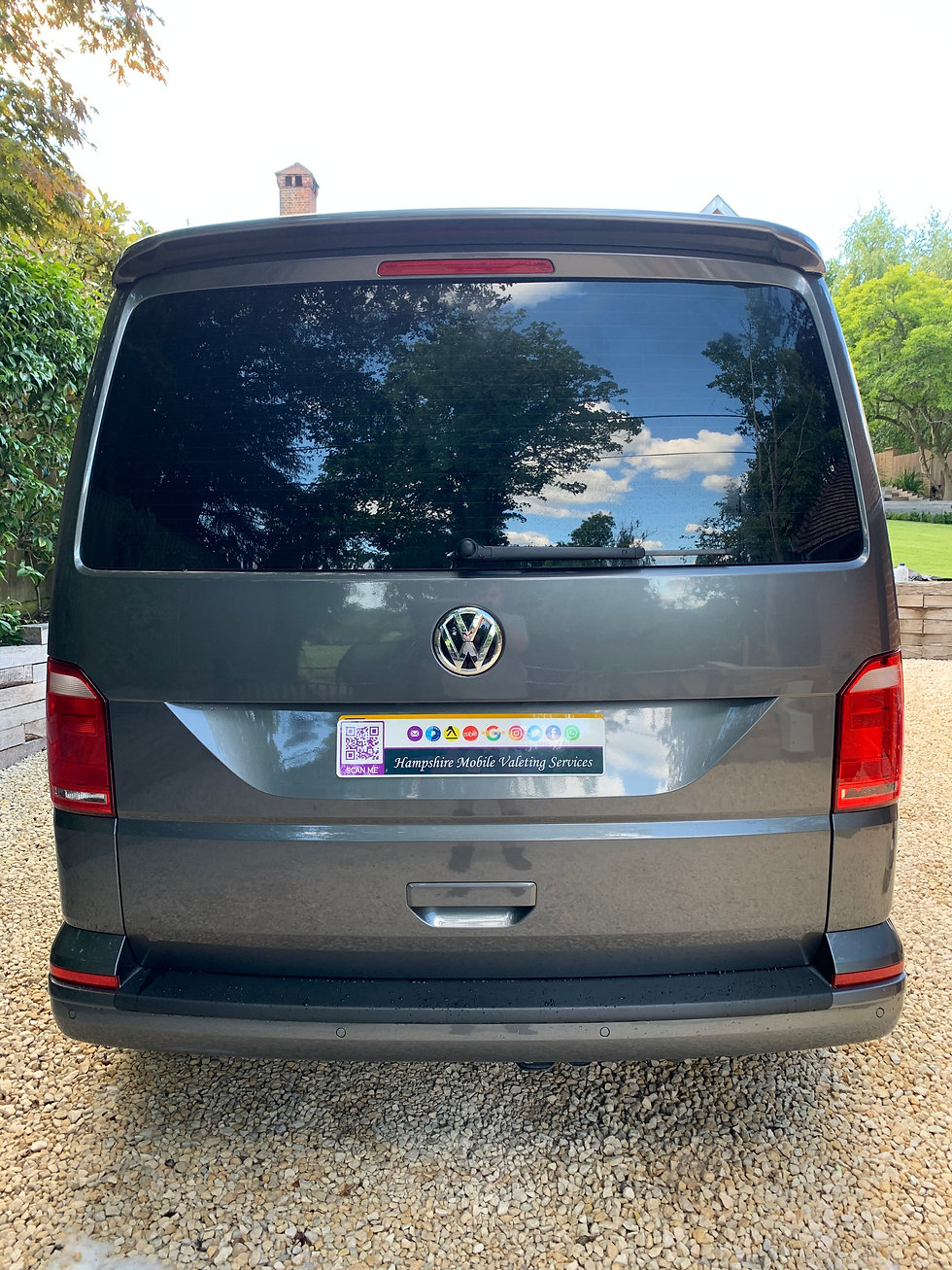 Clean camper van with company display plats with scenic driveway back drop