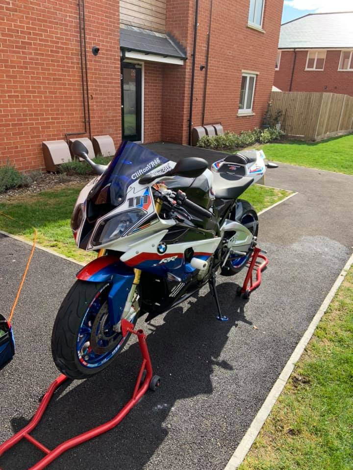 clean motorcycle on peg stands, completed to gold valet standards, grass and pathway backdrop
