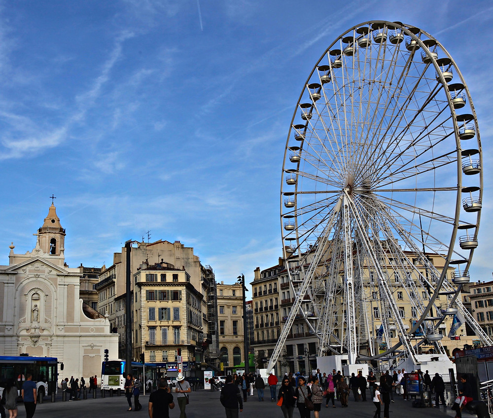 Image of Ferris wheel in an old city plaza.