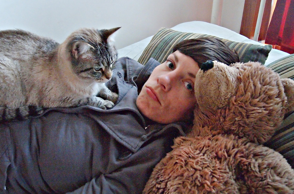 Image of young person lying down with cat and stuffed bear on chest. Raleigh psychotherapy, Katherine Broadway LPC